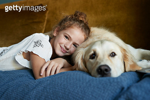 Portrait of girl lying on sofa with her Golden Retriever dog - gettyimageskorea