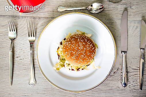 American fast food served with silver cutlery and glass of Champagne. - gettyimageskorea
