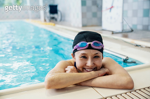 Paraplegic woman is resting inside a pool while training for competitive swimming in Japan - gettyimageskorea