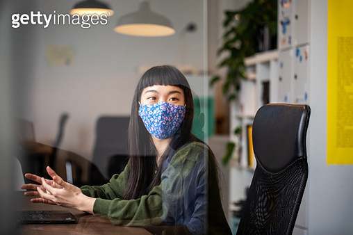 Businesswoman discussing work with colleague through glass shield on desk - gettyimageskorea