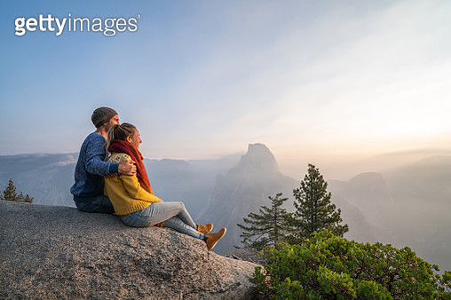 Young couple contemplating sunrise from top of Yosemite valley, USA - gettyimageskorea