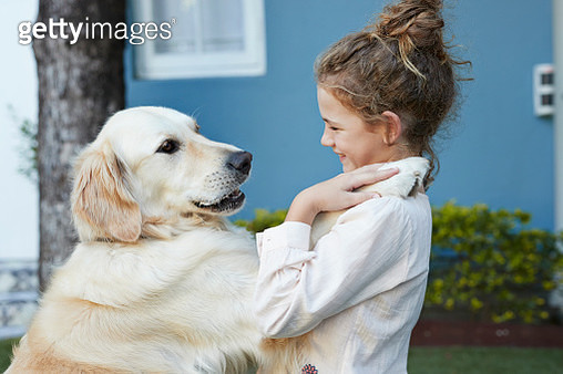 Cute girl laughing and hugging her Golden Retriever dog - gettyimageskorea