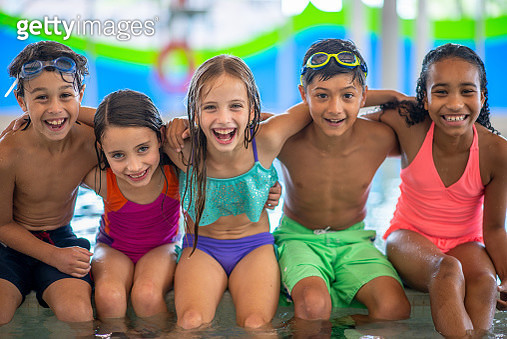 A diverse group of children stop to link arms and pose for a portrait together during a small break from a swimming lesson. They are smiling and having fun. - gettyimageskorea