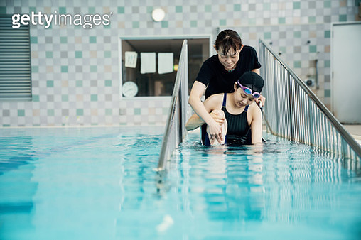 Paraplegic woman in a wheelchair and her coach entering or leaving the pool before or after training for competitive swimming - gettyimageskorea