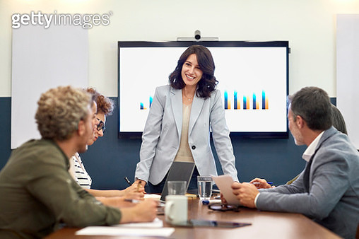 Smiling executive giving presentation to colleagues in board room. Businesswoman is explaining development graph to partners. They are discussing at creative office. - gettyimageskorea