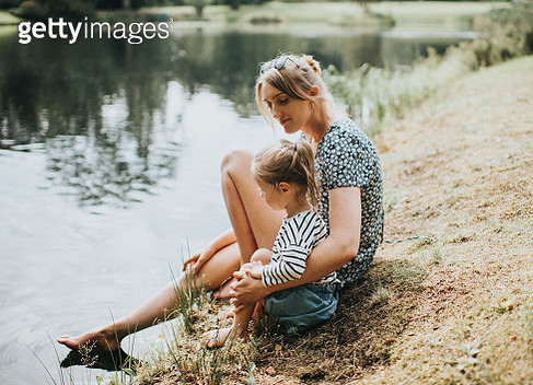 Adult and child together at the edge of a lake. - gettyimageskorea