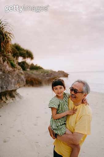 Grandfather cuddling granddaughter on beach at sunset - gettyimageskorea