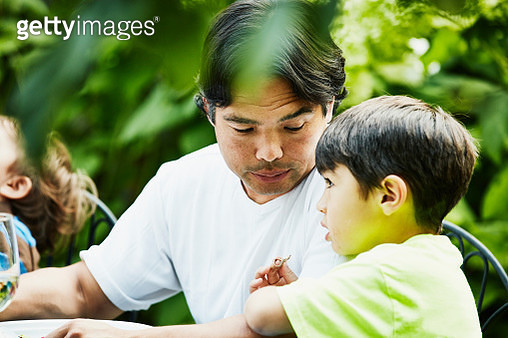 Father in discussion with son during backyard party - gettyimageskorea