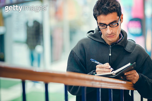 An Asian/Indian mid adult freelancer businessman writes on a business planner and stands by a railing near shopping complex. - gettyimageskorea
