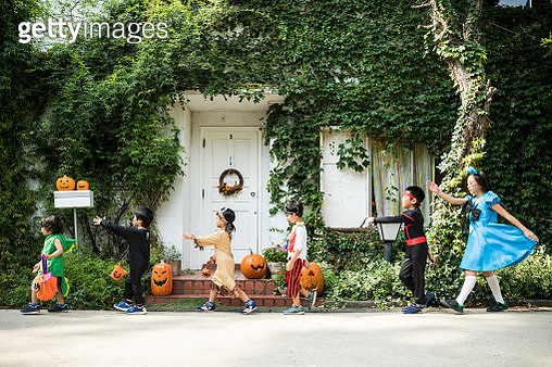 Children marching in front of the house wearing costumes. - gettyimageskorea