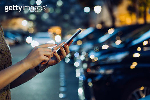 Cropped shot of a woman's hand using smartphone while walking to her car in car park in city at night - gettyimageskorea