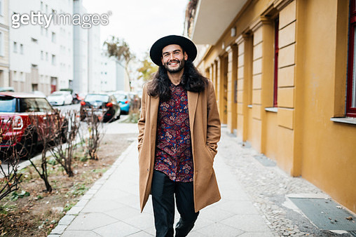 A stylish young man with long hair and a hat on his way to meet some friends. - gettyimageskorea