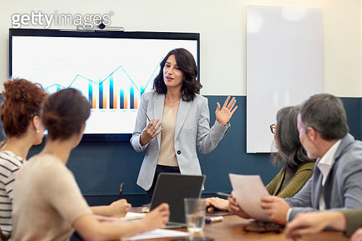 Confident businesswoman giving presentation to colleagues in board room. Entrepreneur is explaining development graph to partners. They are planning at creative office. - gettyimageskorea