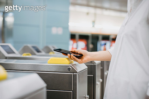 Woman using app device on smartphone to pay for subway ride - gettyimageskorea