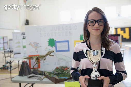 Portrait smiling, confident girl middle school student holding trophy at science fair - gettyimageskorea