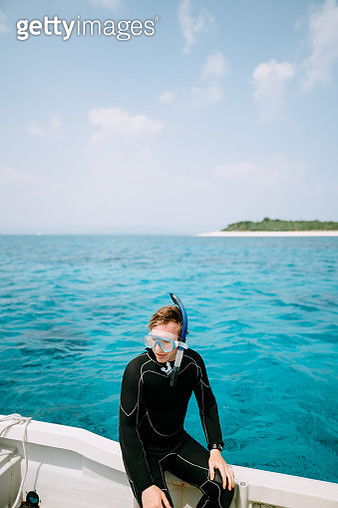 Caucasian man wearing snorkel mask and wetsuit on boat over blue water with tropical island, Aragusuku-jima of the Yaeyama Islands, Okinawa, Japan - gettyimageskorea