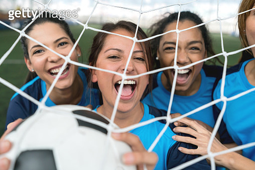 Female soccer team celebrating with excitement a goal they just scored - gettyimageskorea