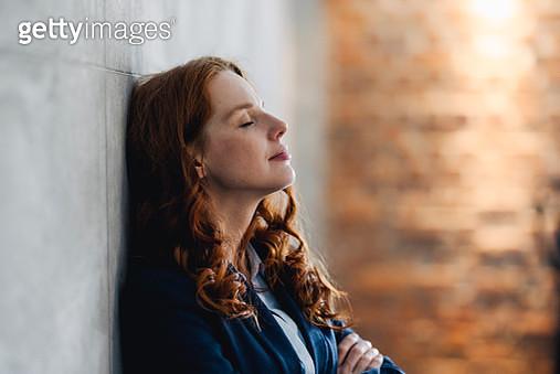 Redheaded businesswoman having a break leaning against a wall in office - gettyimageskorea