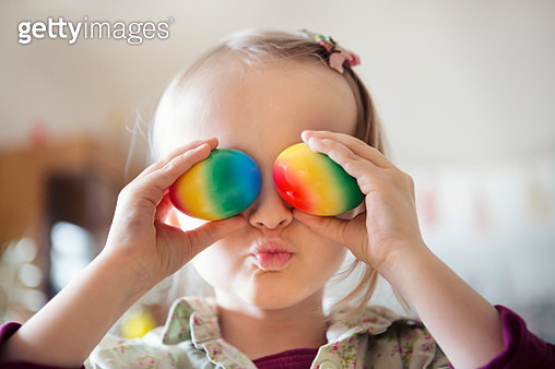Child holding colorful painted eggs over eyes - gettyimageskorea