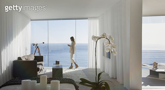 Woman standing on modern luxury home showcase balcony with sunny ocean view - gettyimageskorea