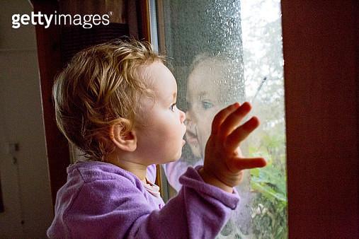 Uk, London, young girl (2-3) watching the rain - gettyimageskorea