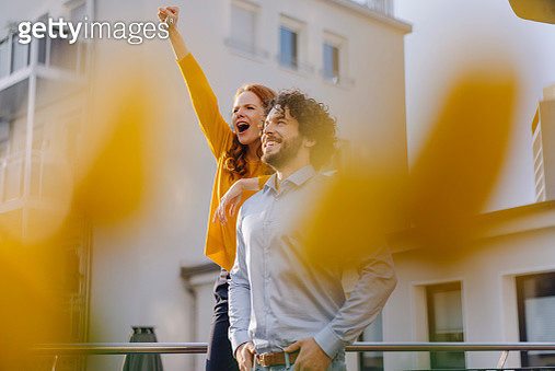 Woman with colleague on roof terrace clenching fist - gettyimageskorea