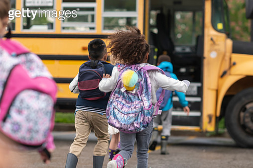 Diverse group of happy children getting on school bus - gettyimageskorea