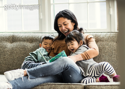 Mother reading to kids on couch - gettyimageskorea