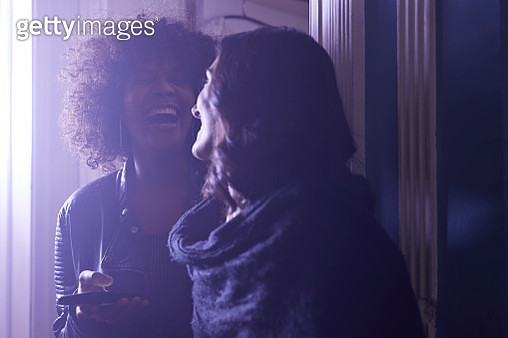 Happy young women looking at smartphone at party - gettyimageskorea