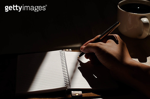 A young person who is writing a journal over a cup of coffee - gettyimageskorea