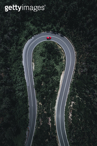Drone image of a hairpin bend in a forest, Italy - gettyimageskorea