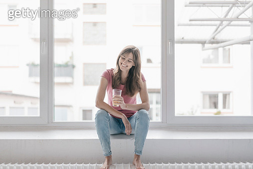 Woman sitting on window sill, holding a glass - gettyimageskorea