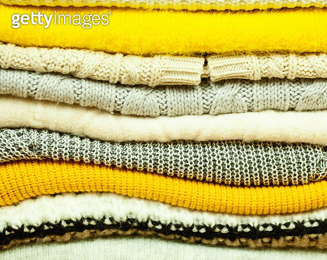 A stack of cozy winter cable knit sweaters in different colors - gettyimageskorea