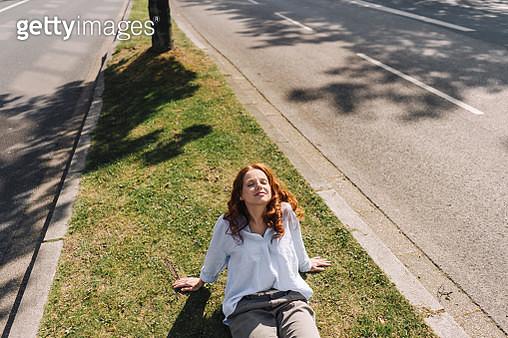 Redheaded woman sitting on grass verge - gettyimageskorea
