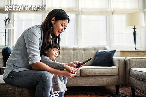 Mother using smartphone with children present - gettyimageskorea