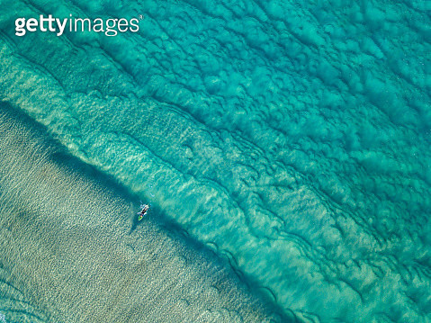 Aerial Viewpoint of clear ocean waters with surfers - gettyimageskorea