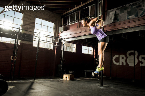 Young woman exercising on gymnastic ring - gettyimageskorea