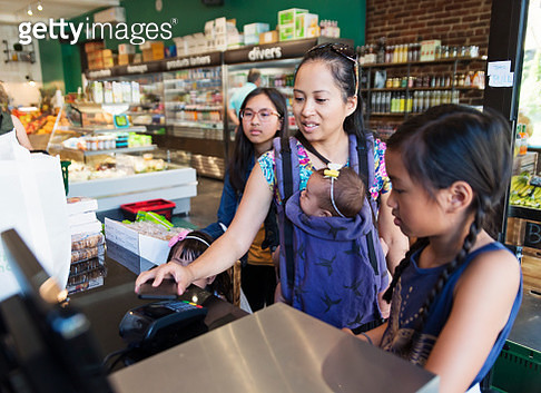 Zero waste oriented small local fruit and grocery store. Family business. Fruits and vegetables are organic and sold without wrapping. Unsold items are use to make juices, smoothies and take-out healthy food. Mother and daughters at check out counter usin - gettyimageskorea