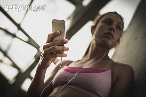 Close up of woman using cell phone while listening music over it. - gettyimageskorea