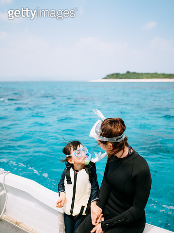 Mother and 4 year old child wearing snorkeling mask, looking at each other on boat, Yaeyama Islands, Okinawa, Japan - gettyimageskorea