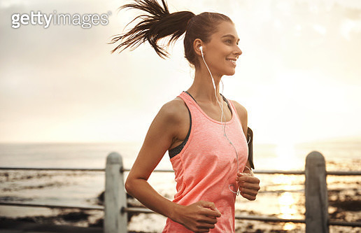 Shot of a young woman running on the promenade at sunset - gettyimageskorea