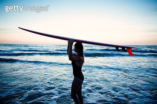 Female surfer carrying surfboard on her head in whitewash - gettyimageskorea