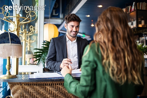 Hotel receptionist assisting guest for checking in - gettyimageskorea