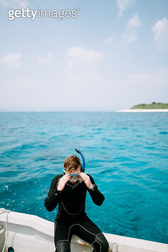 Caucasian man putting on snorkel mask on boat around tropical island with blue water, Aragusuku Islands of the Yaeyama Islands, Okinawa, Japan - gettyimageskorea
