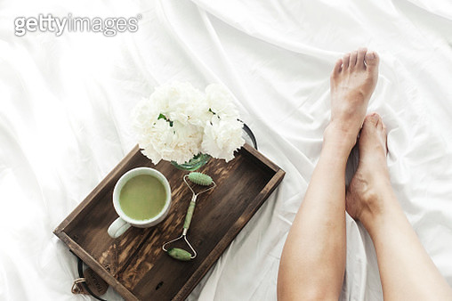 Low section of woman with jade roller and matcha tea in wooden tray on bed - gettyimageskorea