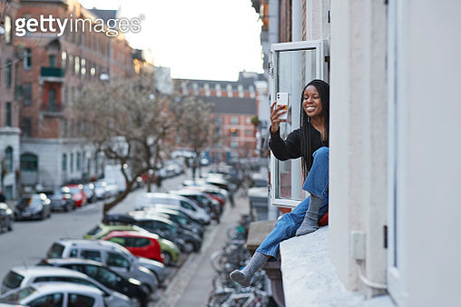 Smiling young woman taking selfie in apartment window during COVID-19 isolation - gettyimageskorea