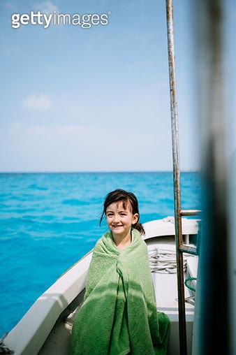 Portrait of cute mixed race preschool girl wrapped in towel, sitting on boat with blue tropical sea, Yaeyama Islands, Okinawa, Japan - gettyimageskorea