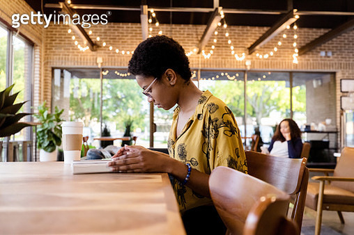 Young African American female college student studies for an exam in coffee shop. - gettyimageskorea