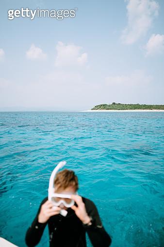 Tropical island on horizon with man putting on snorkel mask, Aragusuku Islands of the Yaeyama Islands, Okinawa, Japan - gettyimageskorea