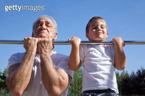 Man and grandson doing chin-ups - gettyimageskorea